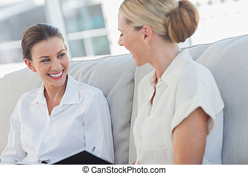 Cheerful businesswomen talking and working together