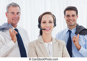 Cheerful call center agent posing with her work team in...
