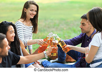 Cheerful carefree group of friends clinking glasses with ...