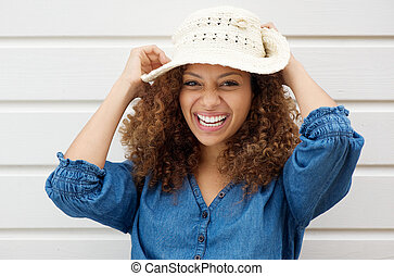 Cheerful carefree woman laughing and wearing summer hat