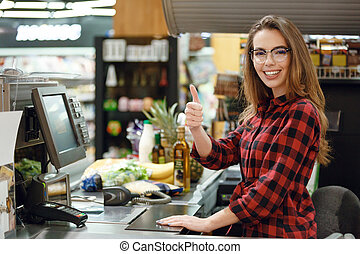Cheerful cashier woman on workspace showing thumbs up. -...