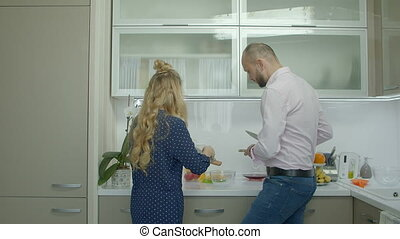 Cheerful casual couple preparing food in kitchen - Positive...