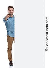 Cheerful casual man pointing forward behind a blank billboard