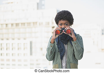 Cheerful casual model using binoculars