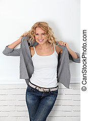 Cheerful casual woman standing on white background
