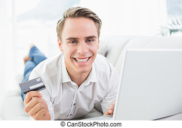 Cheerful casual young man doing online shopping on sofa