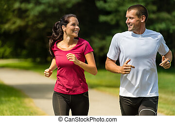 Cheerful Caucasian couple running outdoors - Portrait of...