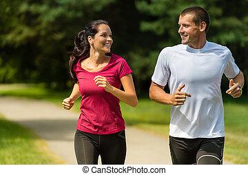 Cheerful Caucasian couple running outdoors - Portrait of...