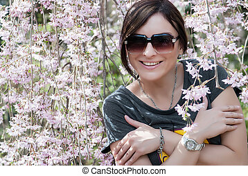 Cheerful caucasian woman under blooming tree