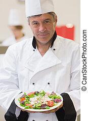 Cheerful chef presenting his salad
