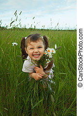 Cheerful child embraces wild flowers