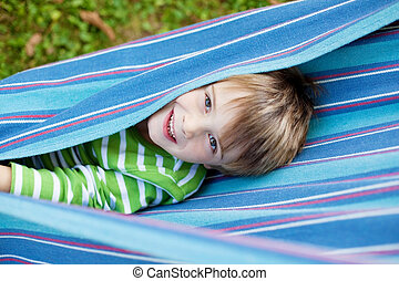 Cheerful child playing in blue hammock
