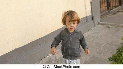 Cheerful child walking on street - Unsupervised cheerful...