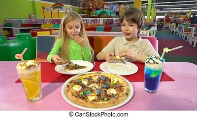 Cheerful children enjoying chocolate pizza during dinner at...