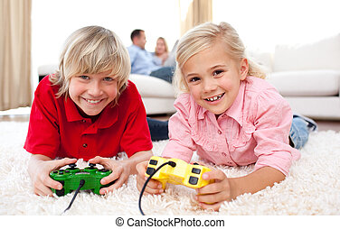 Cheerful children playing video games in the living-room