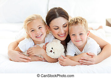 Cheerful children with their mother lying on a bed