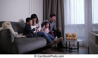 Cheerful chinese family watching soccer game on TV