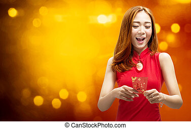 Cheerful chinese woman in traditional dress holding red envelopes