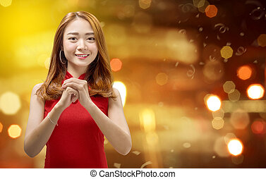 Cheerful chinese woman in traditional dress with congratulation gesture