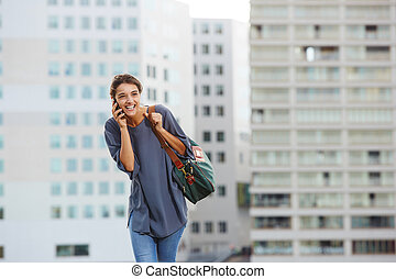 Cheerful city woman talking on mobile phone