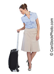 Cheerful classy businesswoman posing with suitcase