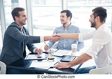Cheerful colleague shaking hands
