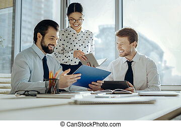 Cheerful colleagues joking during business meeting