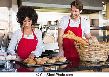 Cheerful colleagues posing with bread