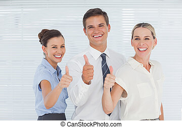 Cheerful colleagues posing with thumbs up