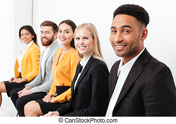 Cheerful colleagues sitting in office