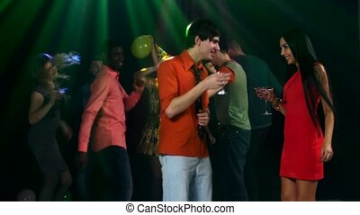 Cheerful company of friends dancing in the background. Couple having fun clink glasses