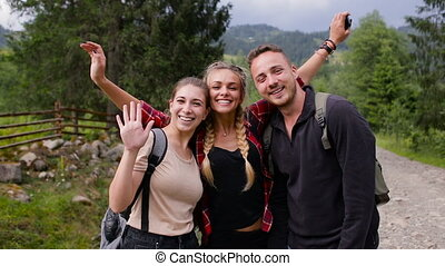 Cheerful company of tourists posing on camera in the mountains