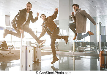 Cheerful comrades jumping in hall