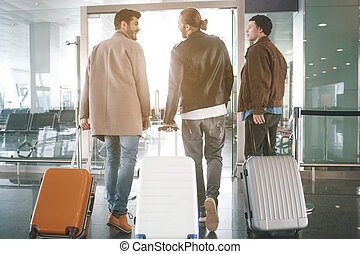Cheerful comrades moving in hall with suitcases