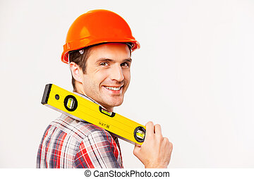 Cheerful construction worker. Rear view of handsome young handyman with carrying work tool on shoulder and looking over shoulder while standing against grey background