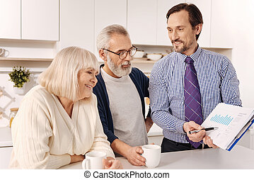 Cheerful consultant discussing contract issues with aged couple of clients