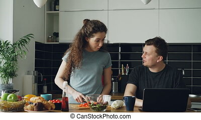 Cheerful couple at table woman dancing and cooking while gives hasband to try red pepper, man sitting working on laptop, he shows something funny on screen