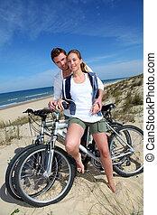 Cheerful couple biking on a sand dune