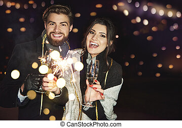 Cheerful couple celebrating new year on the city