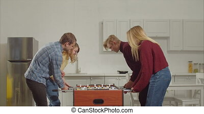 Cheerful joyful young couple defeating opponets in foosball game and celebrating the win with high five while relaxing together at home. Positive teenagers enjoying leisure playing table soccer.