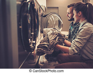 Cheerful couple doing laundry together at laundromat shop...