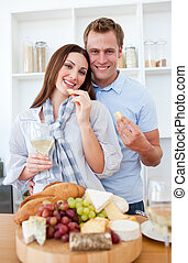 Cheerful couple drinking white wine and eating cheese