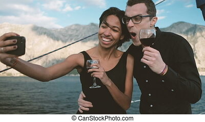 Cheerful couple drinking wine and making funny selfie phone.