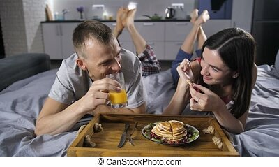 Cheerful couple eating breakfast pancakes in bed - Front...