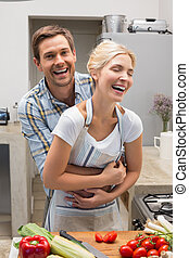 Cheerful couple embracing while preparing food in kitchen