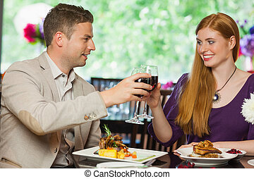 Cheerful couple having dinner together in a classy...