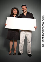 Cheerful couple holding a blank sign