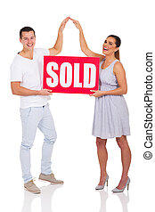 couple holding sold sign for house