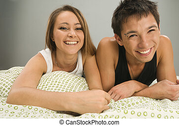 Cheerful couple in bed