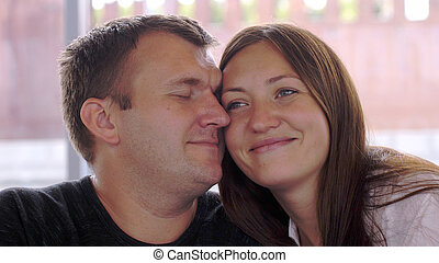 Cheerful couple in love cuddling in a park